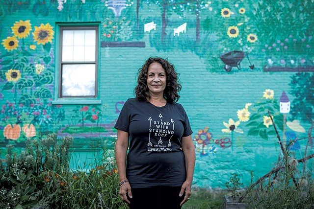 Gina Carrera standing in front of her mural on South Champlain Street - FILE: LUKE AWTRY ©️ SEVEN DAYS
