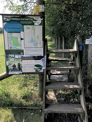 A map and stile along the Trail Around Middlebury - SALLY POLLAK ©️ SEVEN DAYS