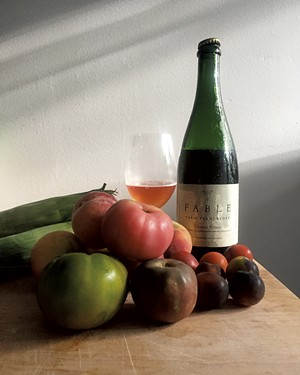 A bottle of Vinous Venus from Fable Farm Fermentory and late summer produce - JORDAN BARRY ©️ SEVEN DAYS