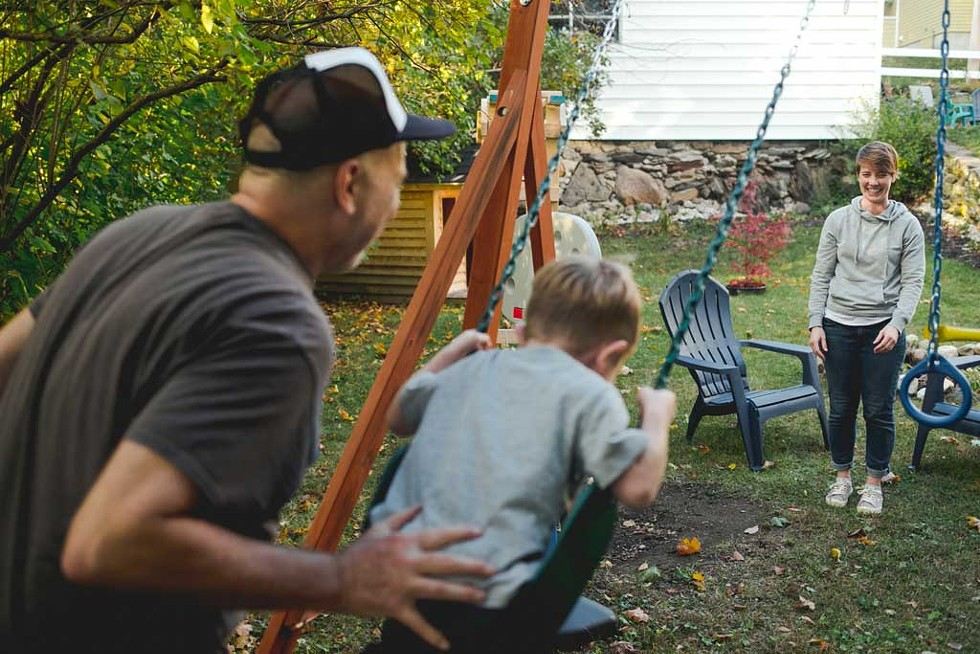 Maresa Nielson and her husband swinging with one of their foster sons - SARAH PRIESTAP