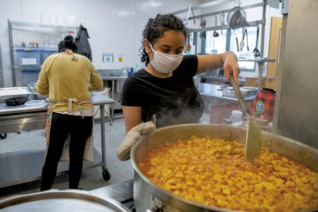 Haydee Miranda of Burlington (right) stirring a pot of curry chicken as Mulu Tewelde prepares more food for a takeout dinner - DARIA BISHOP