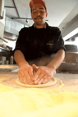 Griffeon Chuba pressing pizza dough. - MATTHEW THORSEN