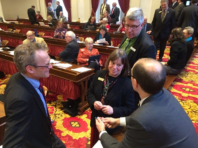 Reps. Willem Jewett (D-Ripton), Helen Head (D-South Burlington) and Tom Stevens (D-Waterbury) confer with Damien Leonard, one of the legislature's lawyers, about the paid sick leave bill. - NANCY REMSEN