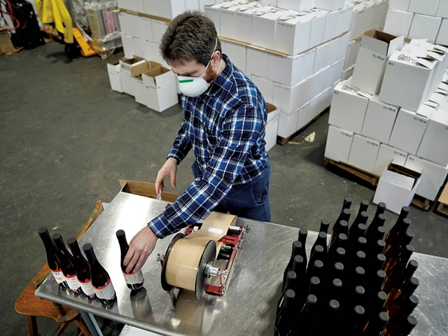 Applying labels to bottles of vermouth - DAVID SHAW