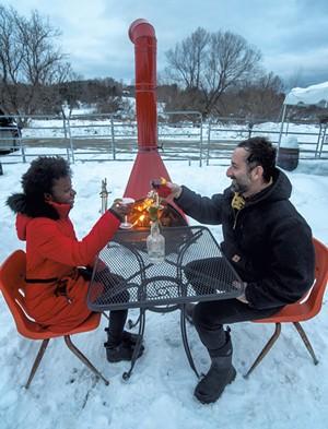 Marlena Tucker-Fishman and Noah Fishman enjoying drinks by Zenbarn's outdoor wood-burning stove - JEB WALLACE-BRODEUR