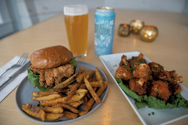 Crispy chicken sandwich with herb fries, cauliflower wings in a housemade maple barbecue sauce, and a Loral Lager by Zero Gravity - DARIA BISHOP
