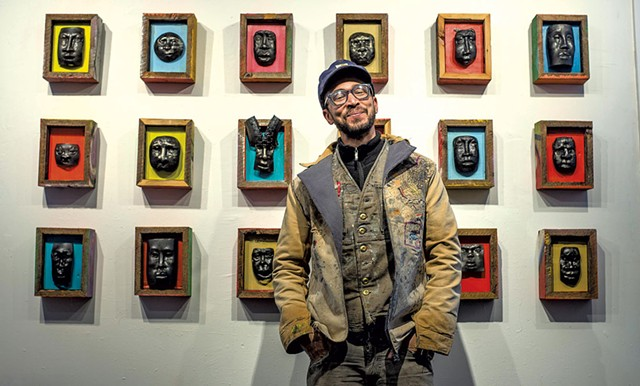 Harlan Mack posing in front of some of his work in a coat and vest he sewed himself at his studio in Johnson - GLENN RUSSELL