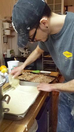 Fernando Mureghias works on a coconut cake. - MELISSA HASKIN