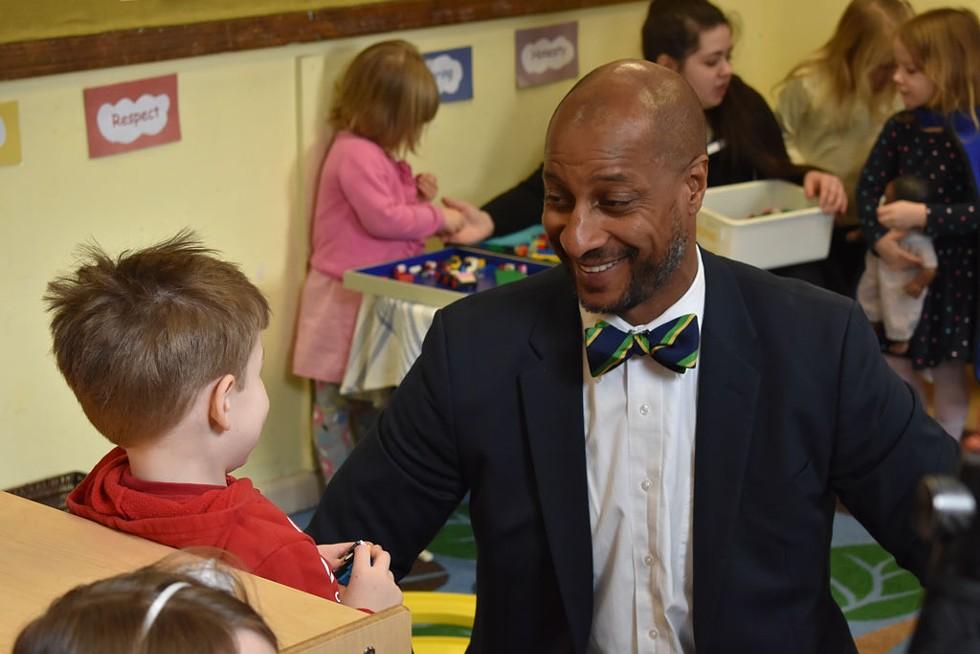 Kyle Dodson talking with a child at the Burlington YMCA - COURTESY OF THE BURLINGTON YMCA