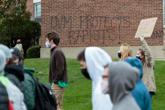 Students march past graffiti criticizing UVM - COLIN FLANDERS ©️ SEVEN DAYS