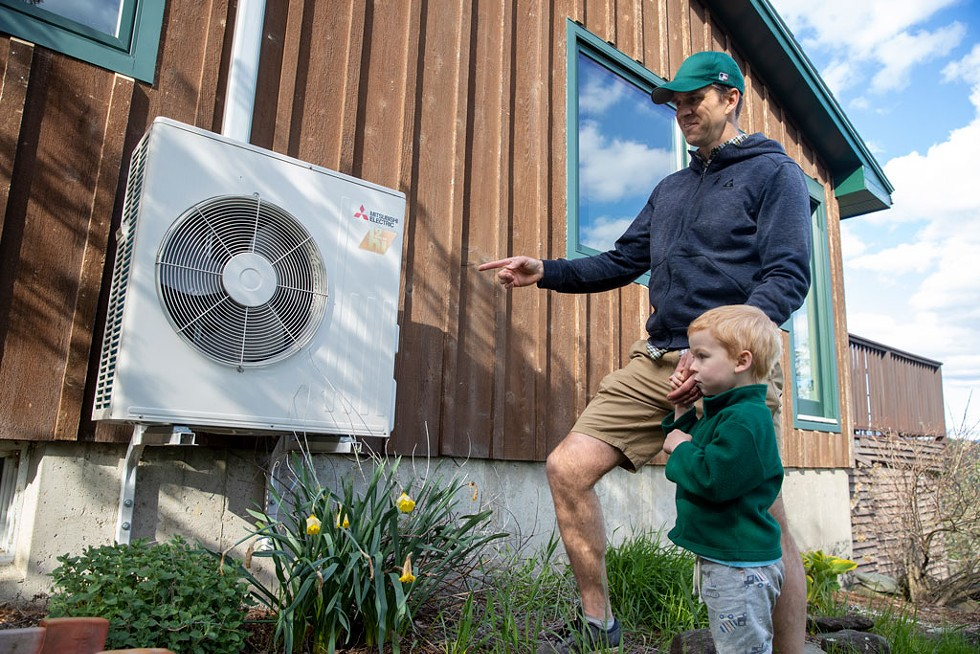 Mike shows off the heat pump to his son Roan - JAMES BUCK