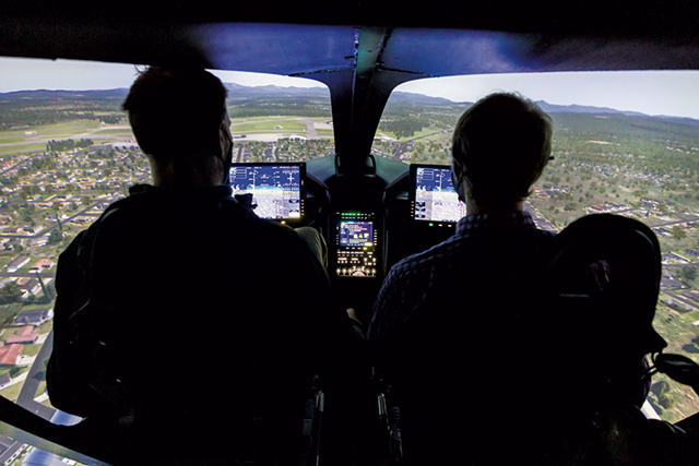 Beta Technologies CEO Kyle Clark operating the company's flight simulator with reporter Derek Brouwer - OLIVER PARINI