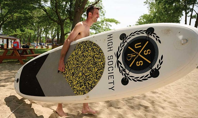 A paddleboarder on the beach - BEAR CIERI
