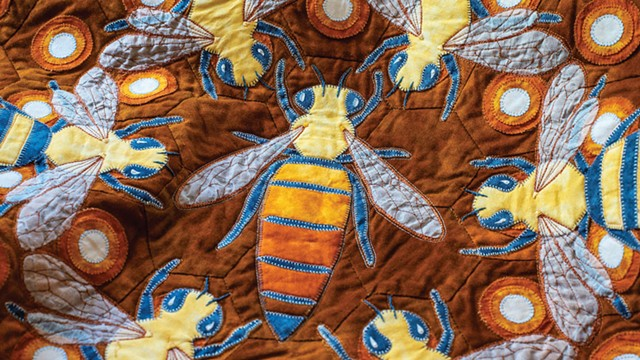 A detail of a bee-themed quilt featuring the hive's queen - GLENN RUSSELL