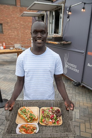 Deng Adiang carrying a tray of freshly prepared food: a kimchi hot dog, a pork belly bánh mì and a strawberry salad - DARIA BISHOP