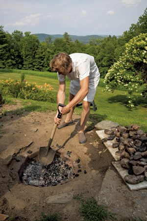 Nevin Taylor preparing the firepit for a clambake - ZACHARY P. STEPHENS