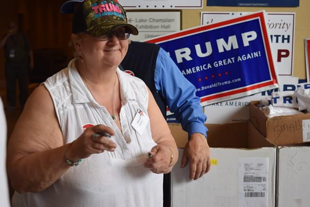 Cheryl Donlan staffs a Donald Trump booth at Saturday's convention. - TERRI HALLENBECK