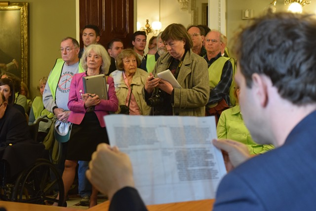 Sen. Tim Ashe (D/P-Chittenden) reads over details of the revised bill as onlookers crowd a Statehouse meeting room. - TERRI HALLENBECK