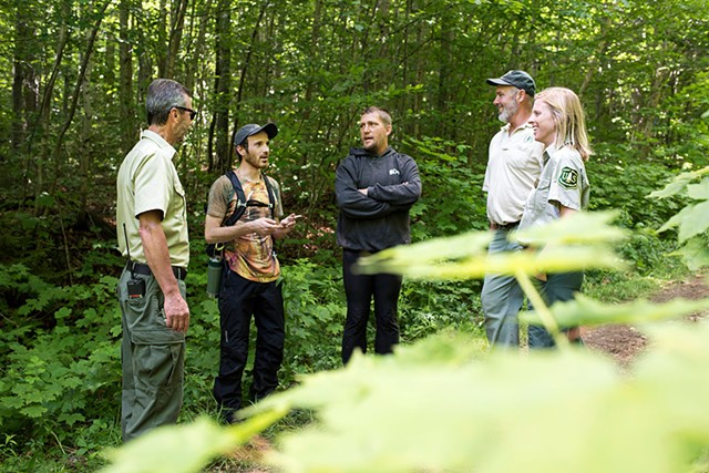 U.S. Forest Service employees talk with participants at the Rainbow Family gathering. - CALEB KENNA
