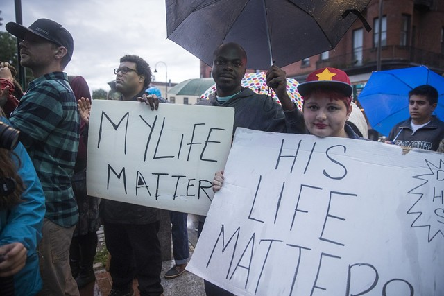 More than 100 people turned out on Saturday for a protest and vigil against police shootings. - JAMES BUCK