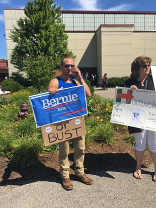 Clay King, left, protests Bernie Sanders' endorsement of Hillary Clinton Tuesday in Portsmouth, N.H. - PAUL HEINTZ