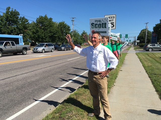 Phil Scott waves to passersby on Shelburne Road in South Burlington on Monday. - TERRI HALLENBECK