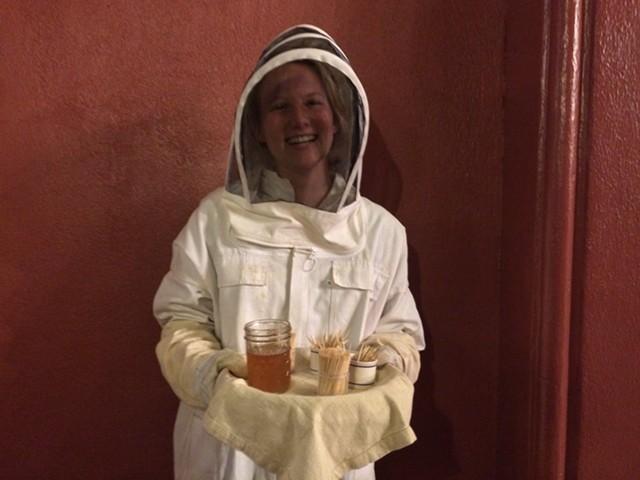 Emily Peters offers guests honey from her professor's apiary. - RACHEL JONES