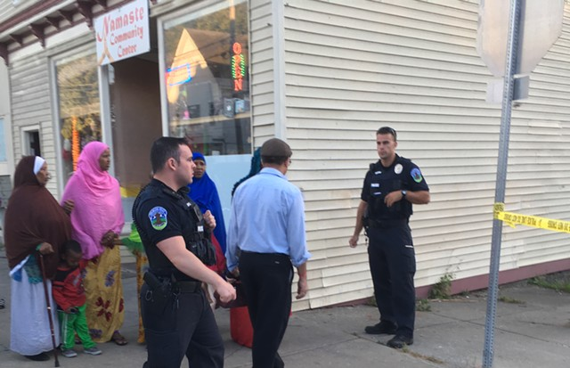 Officers and onlookers by the Namaste Community Center at Union Street and Malletts Bay Avenue - MARK DAVIS