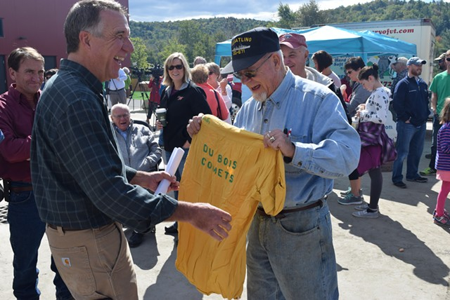 Mick Winter of Barre shows Phil Scott a DuBois bowling team T-shirt from the 1960s at the company's party Saturday. - TERRI HALLENBECK