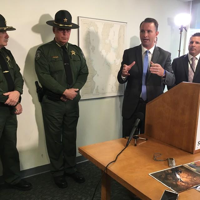 Chittenden County State's Attorney T.J. Donovan speaks as police listen. - MARK DAVIS