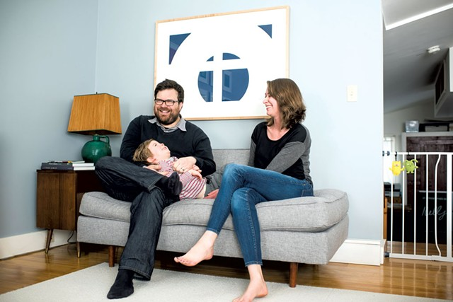 """Jason and Dana Routhier at home; """"SS K-80"""" by Nassos Daphnis hangs over the couch - COURTESY OF SHELBURNE MUSEUM"""