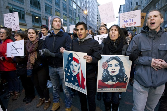 Demonstrators march on the street near a security checkpoint inaugural entrance. - AP PHOTO/JOSE LUIS MAGANA