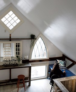 The arched windows in Hopkins' converted barn home were salvaged from the church across the street - SARAH PRIESTAP