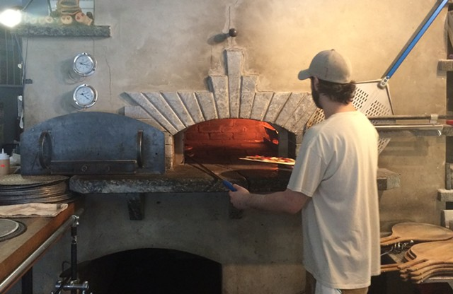 A Folino's staffer puts a pizza in the wood-fired oven - SUZANNE PODHAIZER