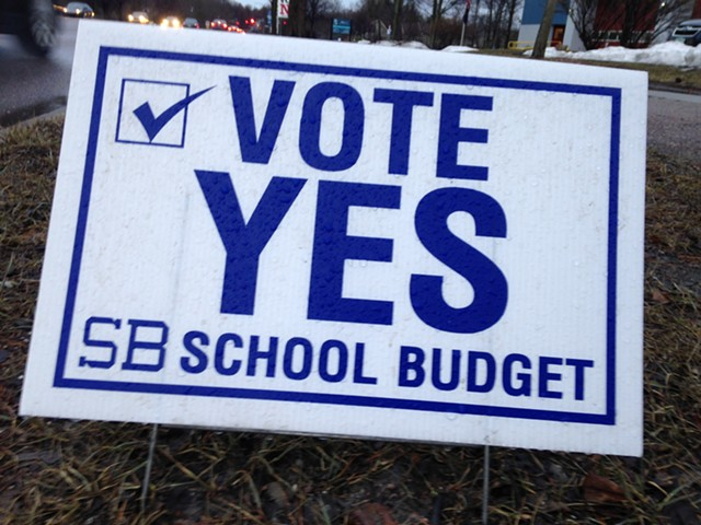 Sign urging voters to approve the budget - MOLLY WALSH