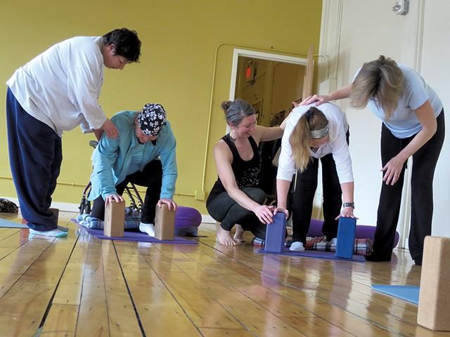 Teresa Wynne (black tank top) assisting yoga students - MATTHEW THORSEN