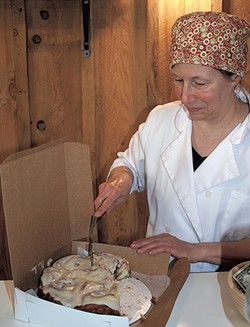 Caroline Demers cutting maple buns at Red House Sweets - SUZANNE PODHAIZER