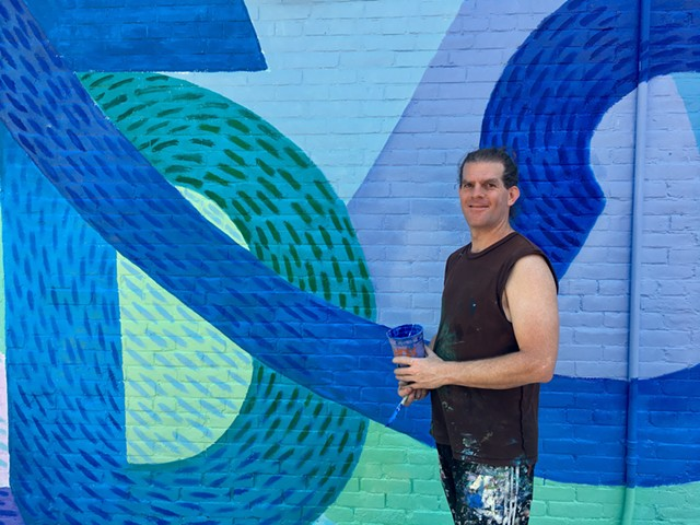 Alex Cook in front of his Cherry St. mural. - SADIE WILLIAMS