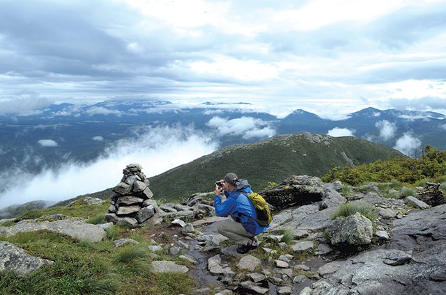 Steve Humphry taking a photo on Algonquin Peak - SASHA GOLDSTEIN