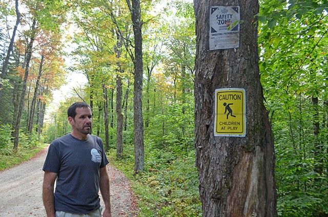 Chris Pike standing near signs he posted - MOLLY WALSH