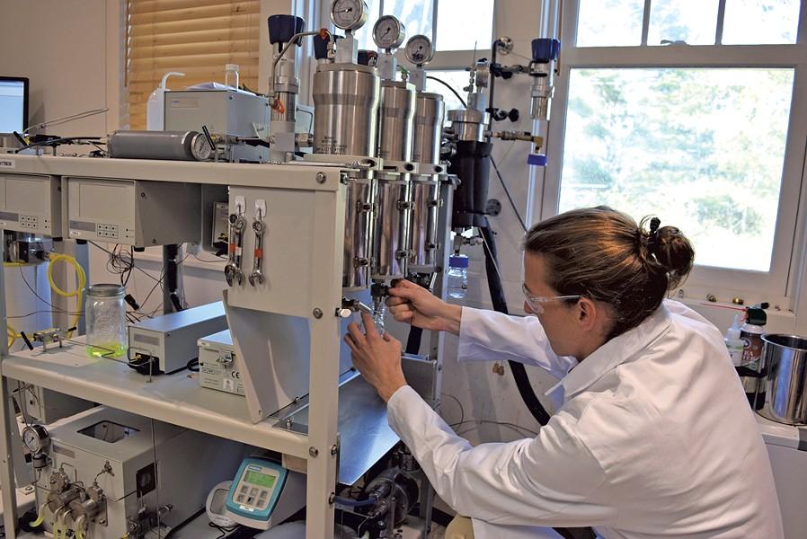 Eric Kawka working with cannabis-testing equipment - TERRI HALLENBECK