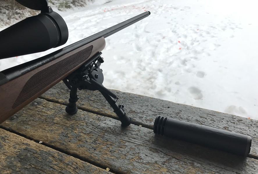 A .308 rifle with a threaded barrel alongside a suppressor. - TAYLOR DOBBS