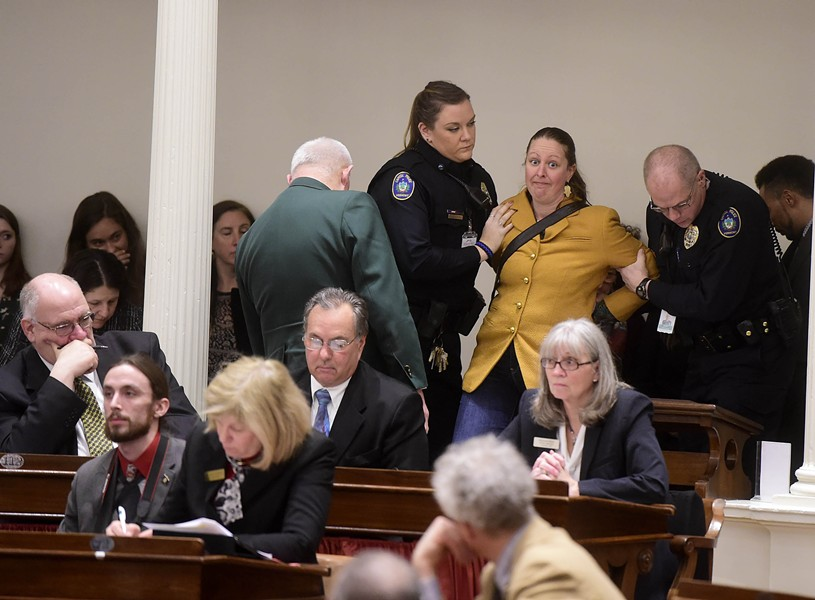 Capitol police escort a protester from the Vermont House chamber as Gov. Phil Scott delivers his budget address. - JEB WALLACE-BRODEUR