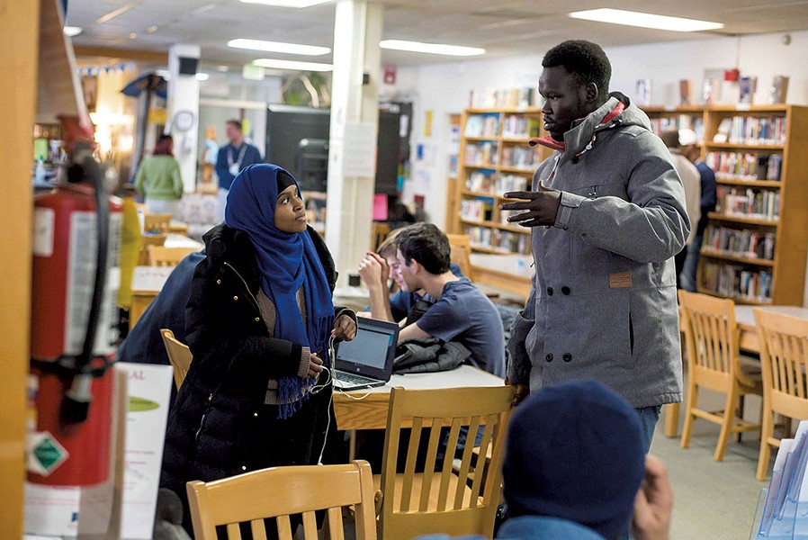 Yuol Herjok of Spectrum Youth & Family Services (right) speaking with Burlington High School senior Halima Said at the school's Spectrum Multicultural Help Desk - GLENN RUSSELL