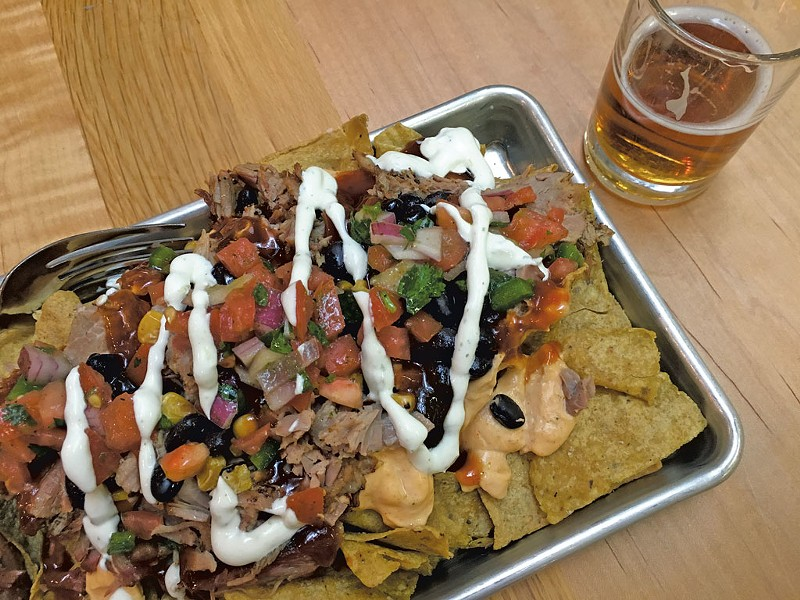 Hickory-smoked pork nachos and beer at the Otter Creek Brewing pub - MELISSA PASANEN