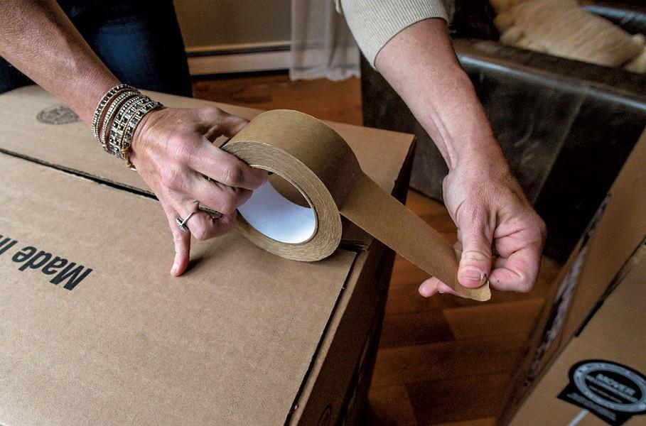 Marlene Simson packing a moving box - GLENN RUSSELL