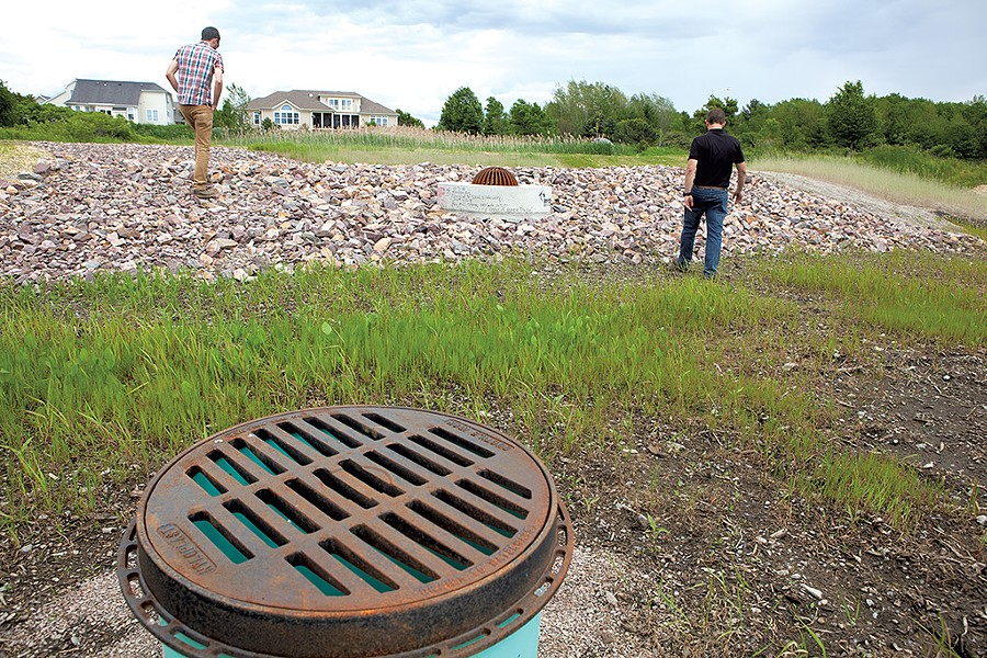 David Wheeler (left) and Tom DiPietro touring a  rebuilt stormwater pond at the Pinnacle at Spear neighborhood - KEVIN MCCALLUM