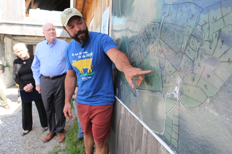 Stony Pond Farm owner Tyler Webb shows Leahy a map of the pastures on his 300-acre property. - KEVIN MCCALLUM