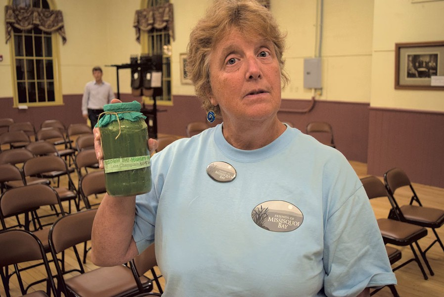 Colleen Curran holding a sample of algae-filled water - TERRI HALLENBECK