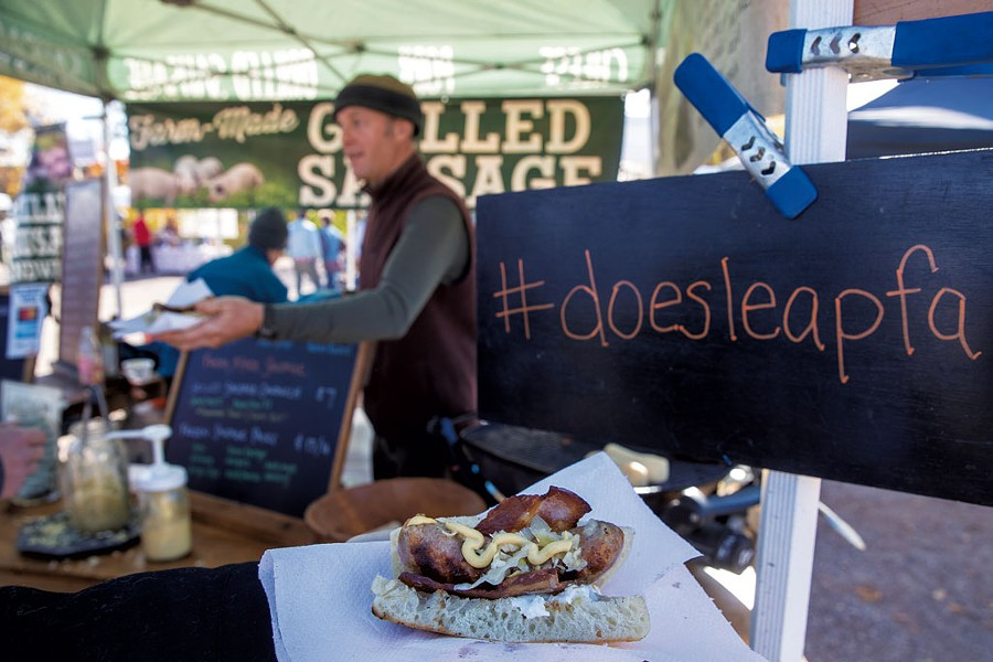 George van Vlaanderen serving a grilled sausage sandwich at the Doe's Leap Farm booth - JAMES BUCK